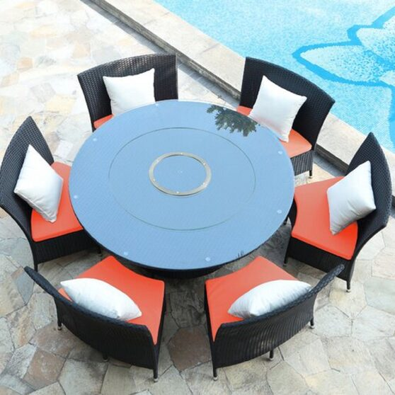 Black 7-piece rattan outdoor dining set with orange and white cushions